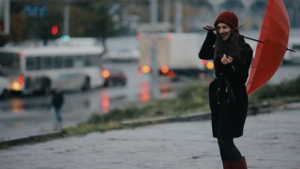 Starker Wind bläst Frau mit rotem Regenschirm nieder