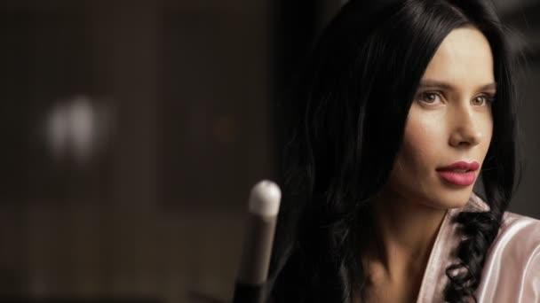 Bruneta žena udělat krásné vlasy s horkou kulmu