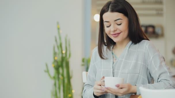 Fiatal nő élvezni kávét inni kávézó
