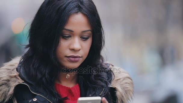 Mladá žena stojí v ulici na zimní zasílání zpráv na mobilní telefon