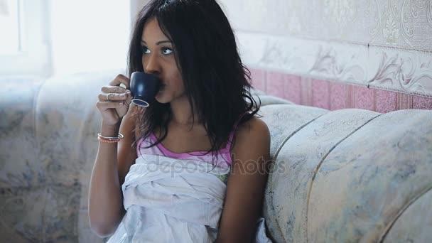Žena, sledování televize a doma pomocí dálkového ovládače