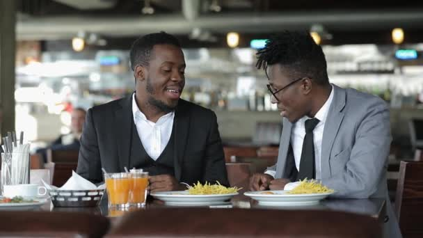 Young african friends businessmans in classical suits conversing in cafe
