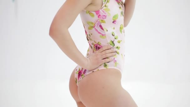 Beautiful attractive model in swimsuit posing at a studio white background