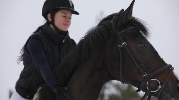 Zärtlichkeit der Frau mit Pferd am Wintertag