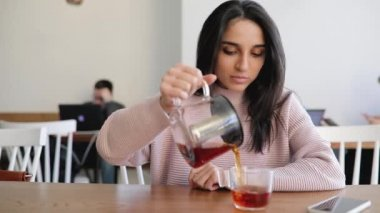 Beautiful woman pouring tea from kettle into glass in a cafe