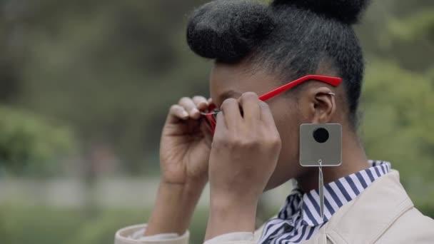 Módní žena stylové brýle v parku zblízka