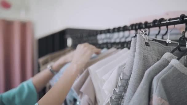 Řadu oblečení na ramínkách v obchodě, ženské ruce choise nosit