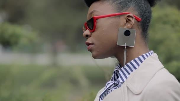 modische Frau trägt stylische Sonnenbrille im Park aus nächster Nähe