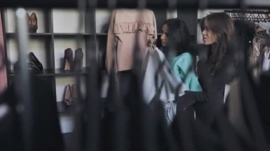 Woman choise clothes in shop, merchandiser help her
