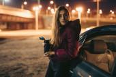Porträt einer Autofahrerin mit Thermosflasche an Auto gelehnt, nachts