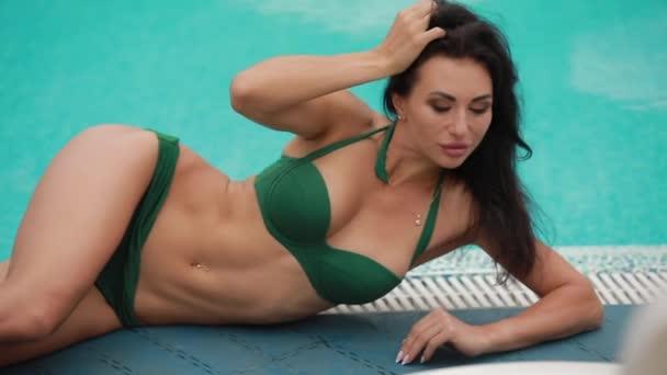 sexy Frau posiert liegend in der Nähe von Schwimmbad
