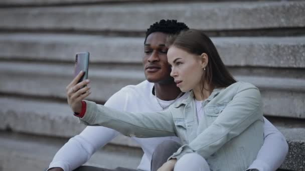 Two multiracial friends makes a selfie photos by smartphone