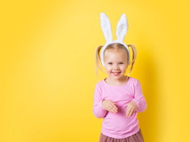 Pretty little girl easter bunny on yellow background