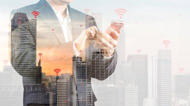 Double Exposure of City Background with Businessman in Suit Using Smartphone Illustrating Wireless Connection and Internet of Things, IOT, Concept