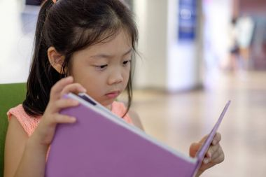 Asian Child Reading Book in Library