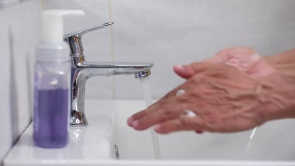 Old man use soap and washing hands under the water tap. Hygiene concept hand detail.