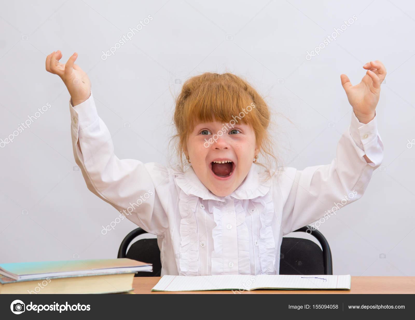 Маленькая девочка на стол весело кричит, руки вверх — стоковое.