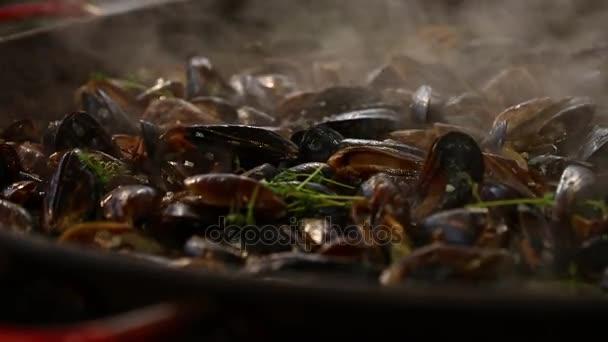 Muscheln in großer Pfanne mit Dampf kochen