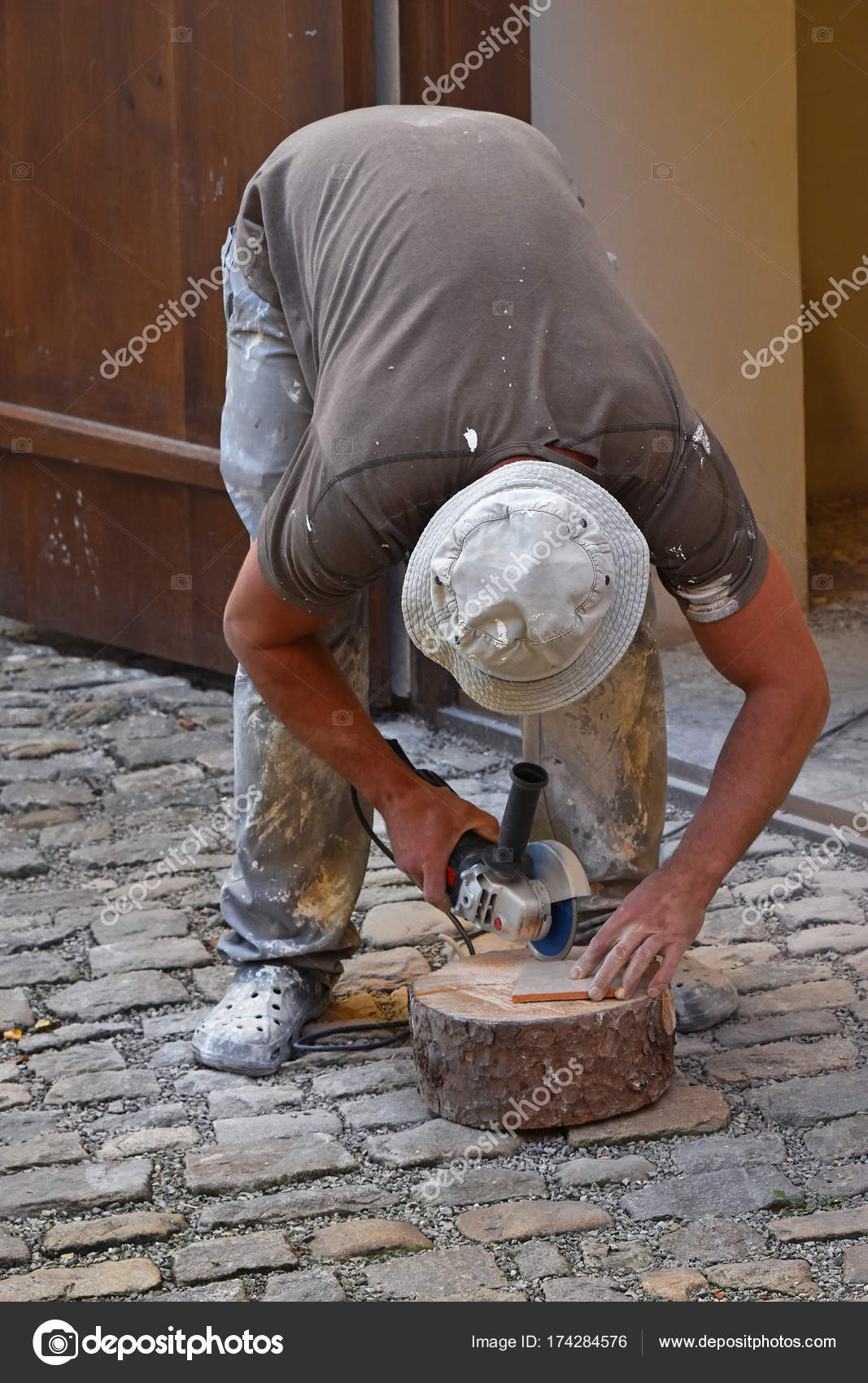 Man Cutting Ceramic Tile With Angle Grinder Stock Photo