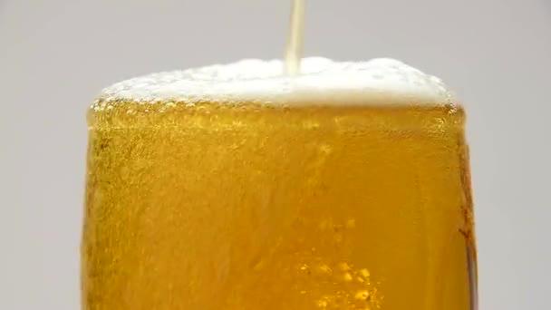 Detailní záběr nalévání piva s bublinkami ve skle