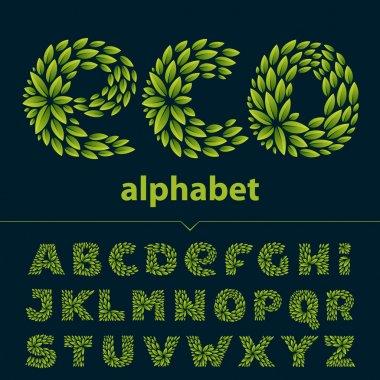 Alphabet logos formed by fresh green leaves.