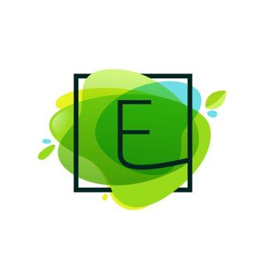 E letter logo in square frame at green watercolor splash backgro