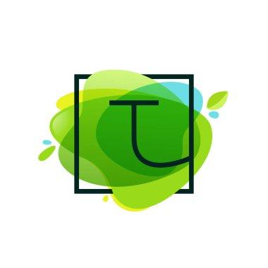 T letter logo in square frame at green watercolor splash backgro