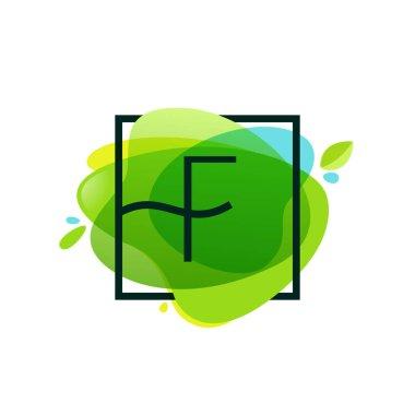 F letter logo in square frame at green watercolor splash backgro