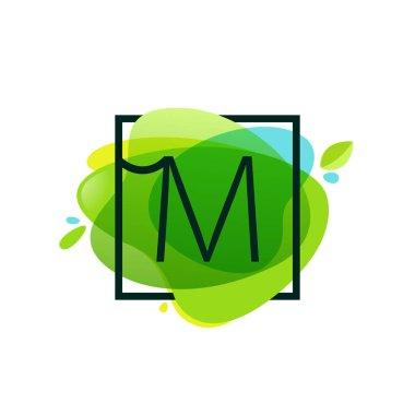M letter logo in square frame at green watercolor splash backgro