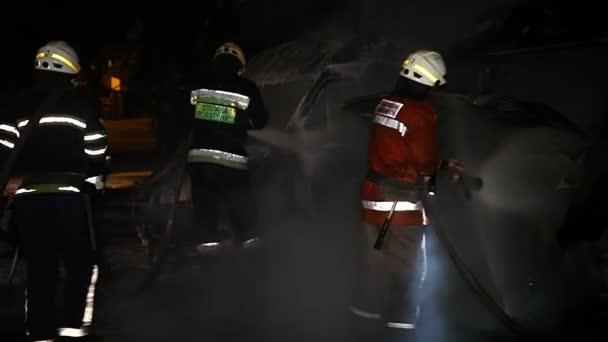 Auto hoří a benzín kape a hoří. Nerozpoznatelný hasič stříká vodu a pěnu na hašení požáru. Loopable seamless animation cinemagraph