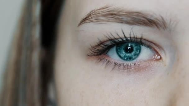 Modrooká dívka otevře své krásné oko a podívá se do kamery