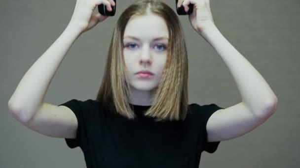 Portrait of teenage girl puts on wireless headphones and enjoying music, dancing