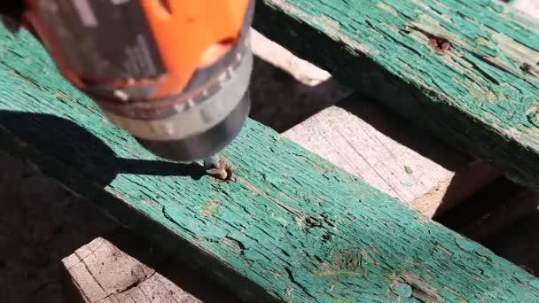 Carpenter odšroubujte šrouby ze starého plotu s šroubovák