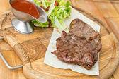 Fotografie gekochtes Steak auf einem Holzbrett