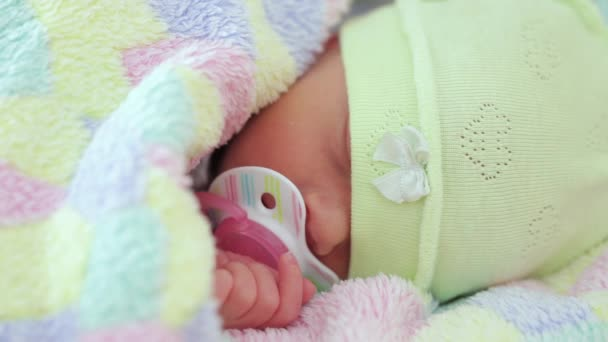 a newborn sleeps with a pacifier