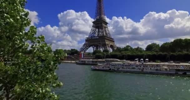 Plavební loď proplouvá za slunečného dne vedle Eiffelovy věže v Paříži ve Francii.