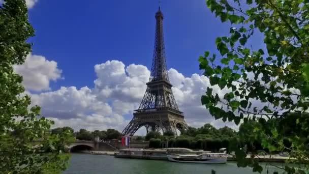 Pohled na Eiffelovu věž mezi stromy. Zpomalený pohyb.