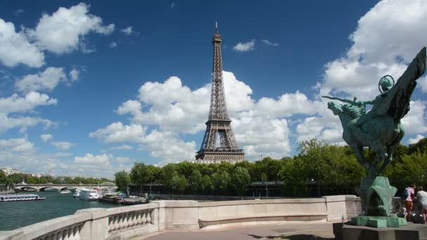 Tourists visiting Bir-Hakeim bridge and France reborn statue with Eiffel tower in the background.