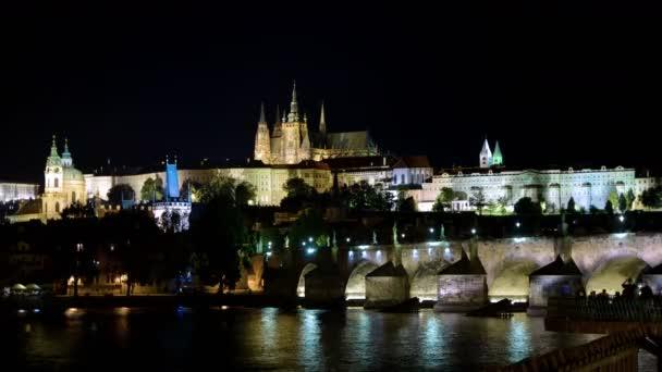 Noční doba plaveb a Karlova mostu. Pražský hrad a katedrála sv. Víta na pozadí.