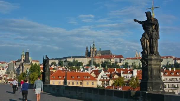 Turisté navštěvují Karlův most za slunečného dne. Pražský hrad a katedrála sv. Víta na pozadí.