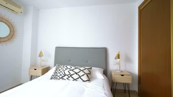 komfortables Hotelschlafzimmer mit Rattan-Kopfteil mit Naturstoffkissen, Makramespiegel, Faser-Nachttisch und einem großen Fenster mit Aussicht. Ferienwohnung mit modernem Boho-Stil.
