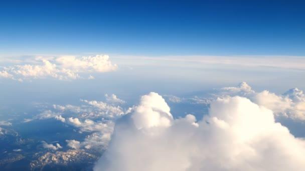 Letecký pohled nad mraky s horami při západu slunce