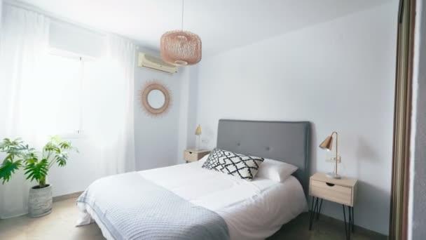 Komfortní hotelová ložnice s ratanovou čelem s přírodním látkovým polštářem, makramovým zrcadlem, vláknovým nočním stolkem a velkým oknem s výhledem. Rekreační byt s Boho moderním stylem.