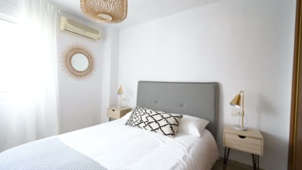 Comfortable hotel bedroom with rattan headboard with natural fabric cushion, macrame mirror, fiber nightstand and a big window with view. Holiday destination apartment with boho contemporary style.