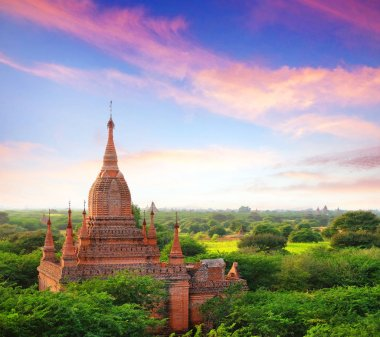 Colorful sky above temples surrounded by green vegetation in old Bagan, Myanmar.