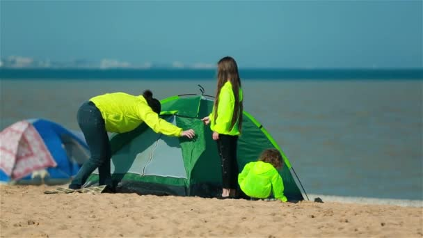 Mother with kids preparing a tent on the beach for families.