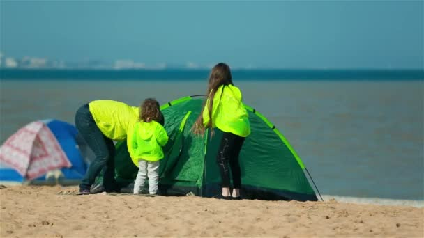 Mom daughter and son go in the green tent on the beach.
