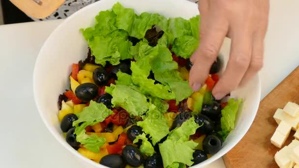 Ženské ruce v misce s nakrájenou zeleninou přidává sýr nakrájíme na kostičky