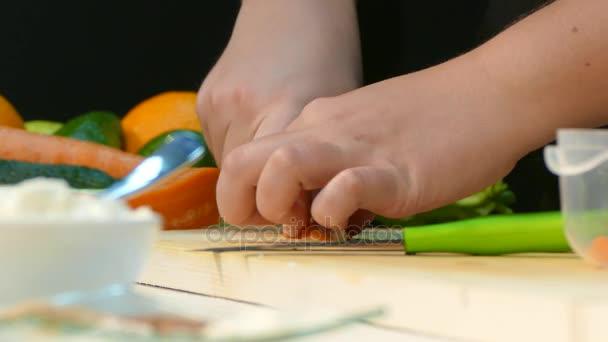 Zenske ruce jsou nožem na dřevěné kuchyňské desce s nožem