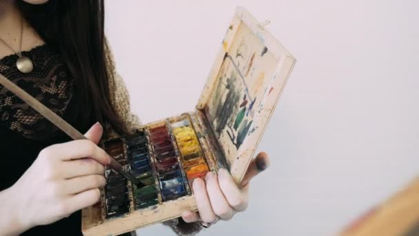 the girl draws a palette of watercolor paints. The process of creating a watercolor painting. Watercolor and creativity